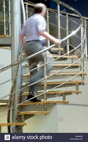 man climbing a stainless steel spiral staircase in a modern open