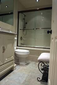 glass door on rectangle bathtub with brown polished metal grab bar