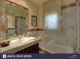 glass shower screen on bath in modern marble bathroom with voile