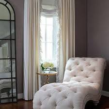 bedroom corner with gray chaise lounge and light wood floors