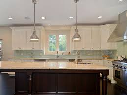 blue glass tile kitchen backsplash with black countertops and a home