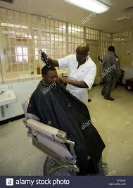 inmate cuts hair of fellow prisoner at the barber shop inside