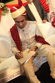 muslim and groom groom signing the marriage certificate at a muslim wedding amir