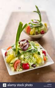 large and small greek salads on white plates sitting on rustic