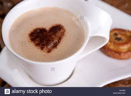 a cup mug of coffee latte with a love heart chocolate sprinkle on