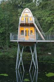 unusual forest cabin on stilts over pond