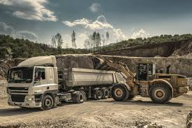 front load loader beside white dump truck free stock photo