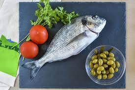 cuisiner cru un poisson cru prêt à cuisiner de brème avec des légumes sur l