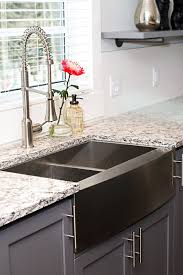 silver stainless steel sink placed on the gray wooden storage feat