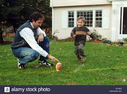 male members of a extended family play football in their front
