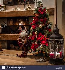 cozy home interior of christmas tree next to fireplace and lantern
