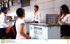 female airport staff checking passport at check in desk stock