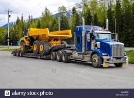 low loader truck carrying a huge dump truck stock photo royalty