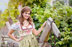 beautiful young woman in traditional bavarian dress standing by an