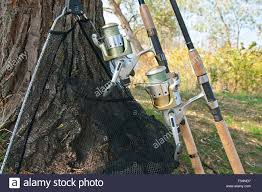 fishing rods with reels and landing net on the natural background