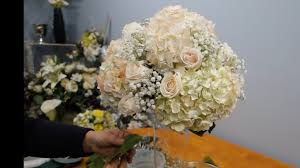 how to make a tall vase centerpiece with white hydrangea and roses