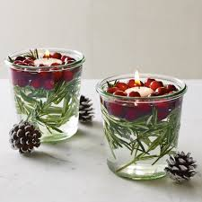 beautiful floating candle with fresh rosemary and cranberries