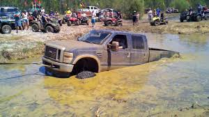 watch as this massive ford mud truck gets pulled from the grasp of