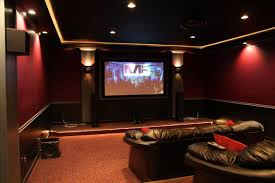 basement home theater with recessed lights and wall sconces