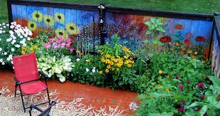 i revived our garden fence by painting flowers on it Garden Mural Ideas