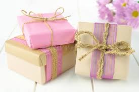 wrapping boxes gift boxes with brown and pink wrapping on white wood stock photo