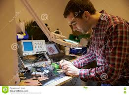 electrical engineer soldering circuit board at work bench stock
