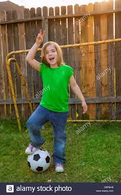 blond little soccer player happy in backyard with ball stock
