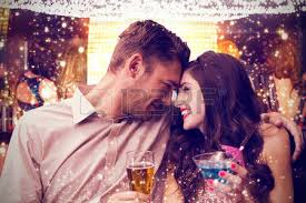 circle of love  Cute couple drinking against gold and red lights