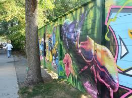 egr as i walk toronto side view of a street art mural on a wall beside a sidewalk the closest