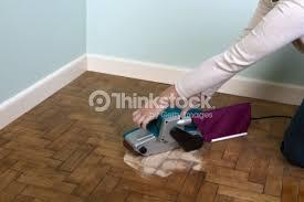 belt sander to sand parquet floor closeup stock photo