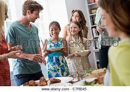 multi generation family gathering around kitchen island stock
