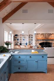 rustic blue kitchen cabinet with stone wall and fireplace kitchen