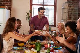 dinner host host and friends pass food round the table at a dinner party stock