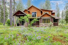 mountain cabin home wood exterior with forest and flowers stock