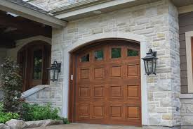 traditional wooden garage doors and coach lights enhance this
