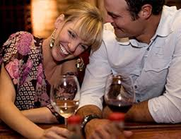 A man and a woman share a laugh over a glass of wine EliteSingles