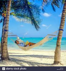 young woman sleeping in hammock between palm trees on caribbean