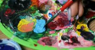 woman artist mixing oil paint on a palette with a paintbrush from
