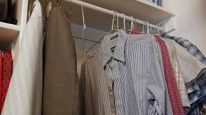 a closet dolly shot of mens dress shirts hanging up in a closet stock video