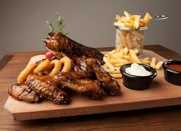 meal of chicken wings and ribs with fries stock image image of