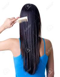 rear view of young combing her healthy long hair isolated