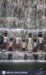 statues of women holding jars standing under waterfall in rock