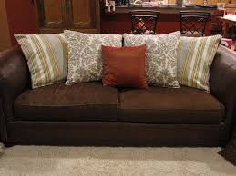 brown sofa with pillows on the wooden floor inside modern natural