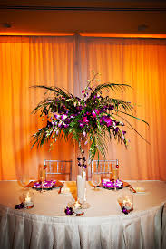 purple cymbidium orchids and palm tree leaf centerpiece flowers