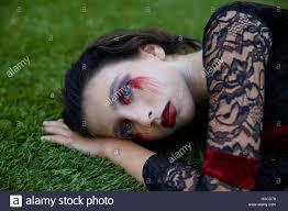 halloween kid custome with bloody makeup on backyard turf