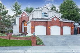 luxury house exterior with red brick wall trim with three car