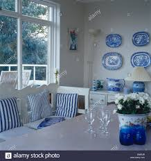collection of blue white plates on wall of dining room with blue