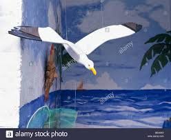 up of wooden seagull mobile against sea mural on garden wall