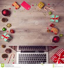 laptop computer with christmas decorations on wooden background