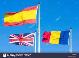 3 flags flying romanian flag spanish flag union jack flag against